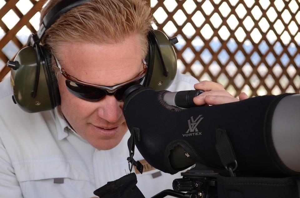 Man looking through spotting scope on a shooting range