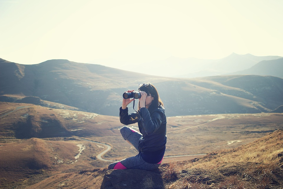 Woman hiking and using binoculars to look into the distance